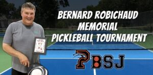 A man holding a paddle and a framed award standing on a pickleball court next to the words Bernard Robichaud Memorial Pickleball Tournament PBSJ